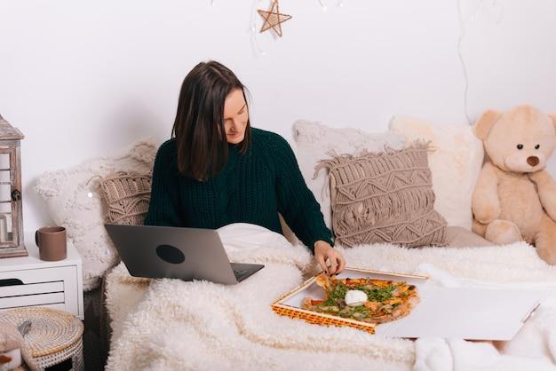 Młoda kobieta pracuje w domu i delektuje się zamówioną pizzą.
