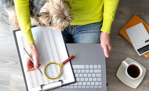 Młoda kobieta pracuje w domu. jest ze swoimi psami