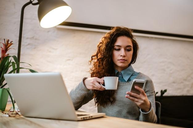 Młoda kobieta pracuje w domu lub w małym nowoczesnym biurze.