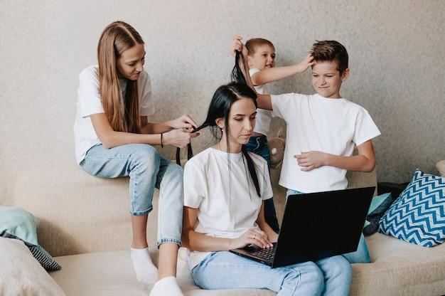 Młoda kobieta pracuje w domu z laptopem razem z dziećmi, dzieci chcą porozumiewać się z matką, hałasować i przeszkadzać w pracy