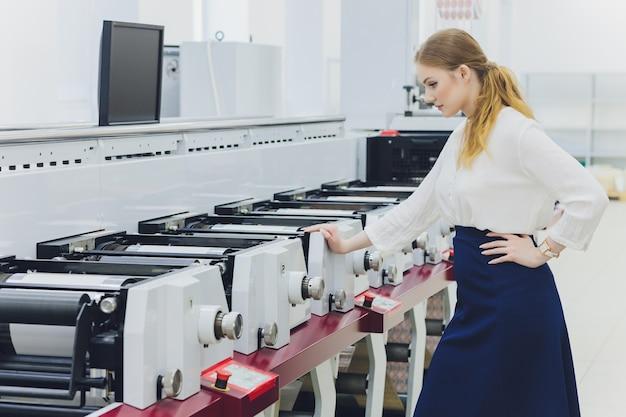 Młoda kobieta pracuje w drukarni. prasa drukarska.