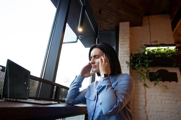 Młoda kobieta pracuje w kawiarni przed laptopa cierpi na przewlekłe codzienne bóle głowy