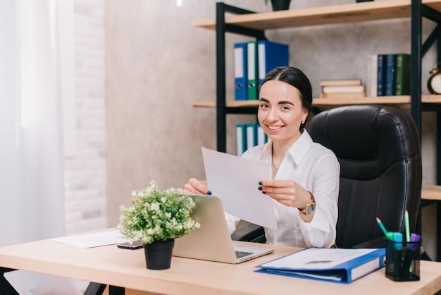 Młoda kobieta pracuje z dokumentami w biurze