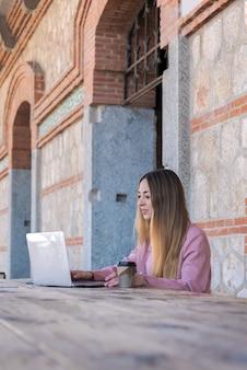 Młoda kobieta pracuje z jej laptopu i telefonu komórkowego obsiadaniem przy drewnianym stołem na ulicie