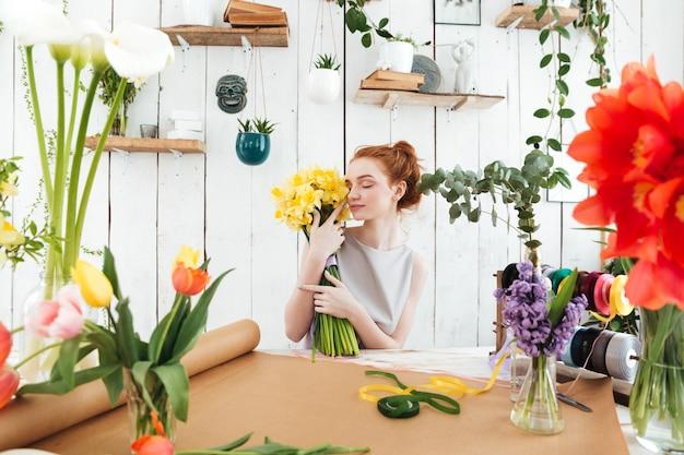 Młoda kobieta pracuje z kwiatami w warsztacie
