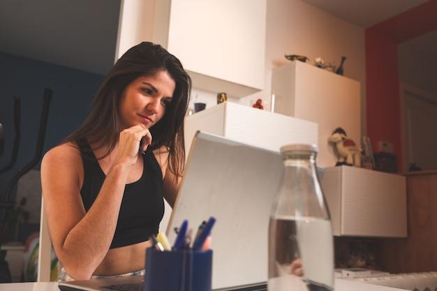 Młoda kobieta pracuje z laptopem w domu na sobie ubrania sportowe