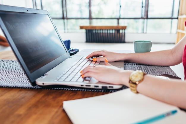 Młoda kobieta pracuje z laptopem w kuchni w domu.
