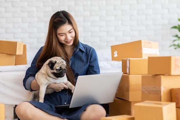 Młoda kobieta pracuje z laptopem w pokoju pełnym pudełka
