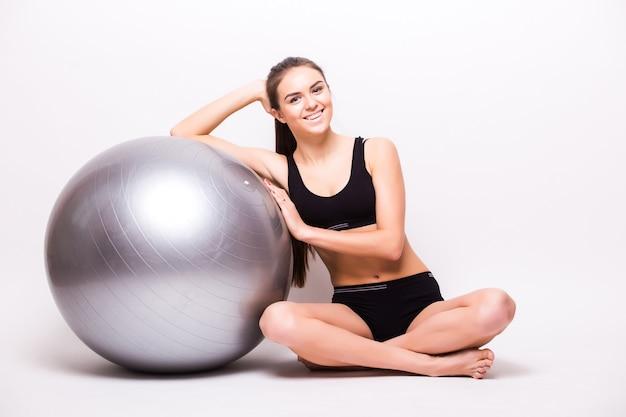 Młoda kobieta pracuje z piłką na białym tle na białej ścianie