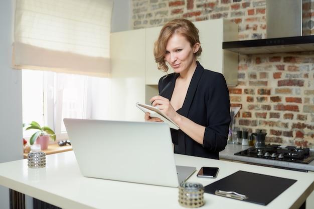 Młoda kobieta pracuje zdalnie na laptopie w kuchni. dziewczyna robi notatki do notesu raportu kolegi z wideokonferencji w domu.