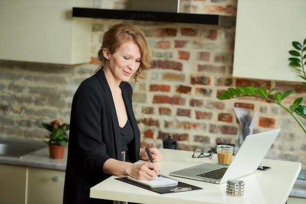 Młoda kobieta pracuje zdalnie na laptopie w kuchni. kobieta szefowa jest zadowolona ze swoich pracowników podczas wideokonferencji w domu. nauczyciel piszący odpowiedzi uczniów podczas wykładu online.