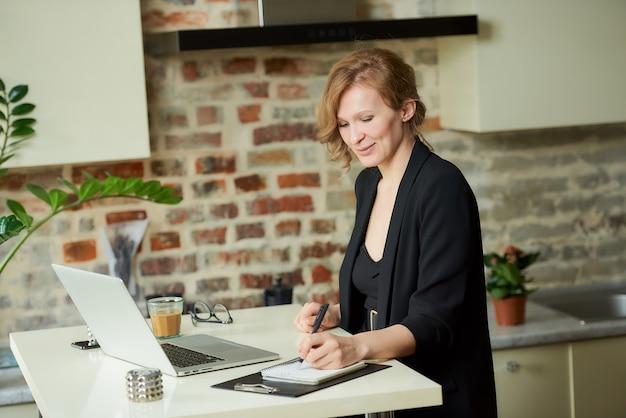 Młoda kobieta pracuje zdalnie na laptopie w kuchni. kobieta szefowa jest zadowolona ze swoich pracowników podczas wideokonferencji w domu.