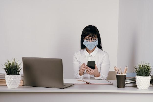 Młoda kobieta pracuje zdalnie w biurze w masce ochronnej podczas epidemii