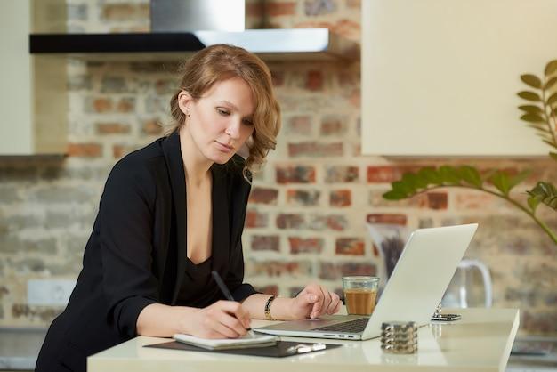 Młoda kobieta pracuje zdalnie w swojej kuchni. urocza dziewczyna robi notatki w zeszycie podczas wideokonferencji w domu. nauczycielka przygotowująca się do wykładu online.
