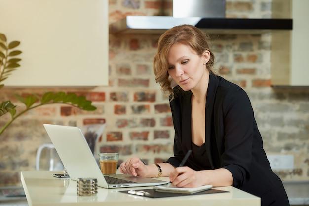 Młoda kobieta pracuje zdalnie w swojej kuchni. urocza dziewczyna robi notatki w zeszycie podczas wideokonferencji w domu.