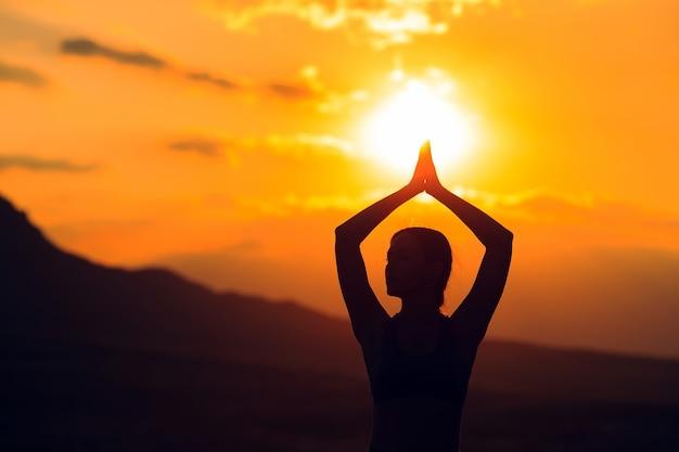 Młoda kobieta praktykujących jogę o zachodzie słońca w pięknej górskiej lokalizacji.