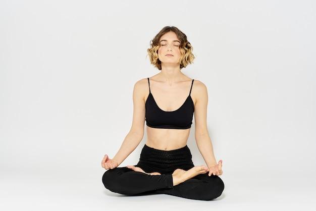 Młoda kobieta praktykuje asan jogi na białym tle