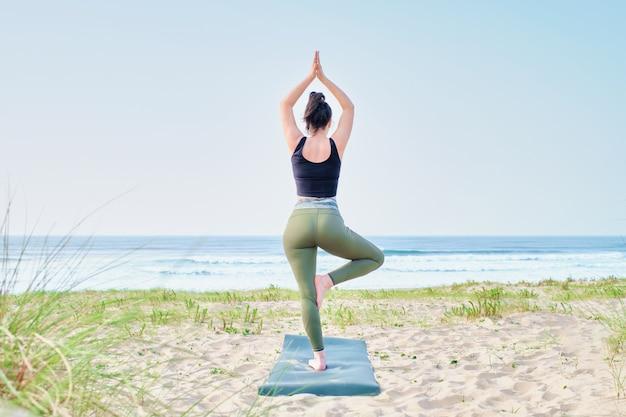 Młoda kobieta praktykuje jogę na plaży, patrząc na morze