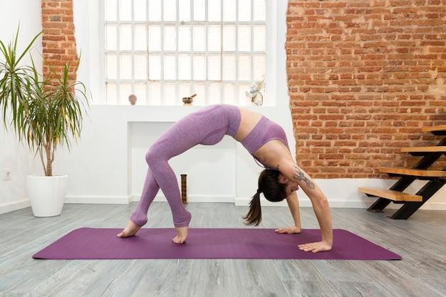Młoda kobieta praktykuje jogę w domu. ona wykonuje ćwiczenie bridge. pojęcie zdrowego stylu życia. miejsce na tekst.