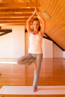 Młoda kobieta praktykuje jogę w dużym studio na poddaszu.