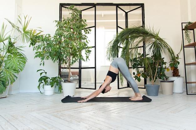 Młoda kobieta praktykuje jogę w pokoju z roślinami.