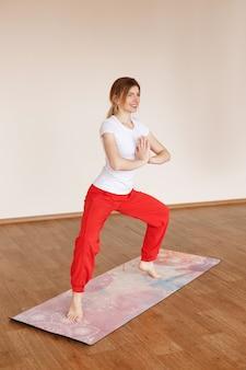 Młoda kobieta praktykuje jogę w swoim pokoju