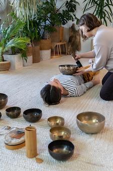 Młoda kobieta praktykuje masaż dźwiękowy z tybetańskimi misami do śpiewania koncepcja medycyny alternatywnej