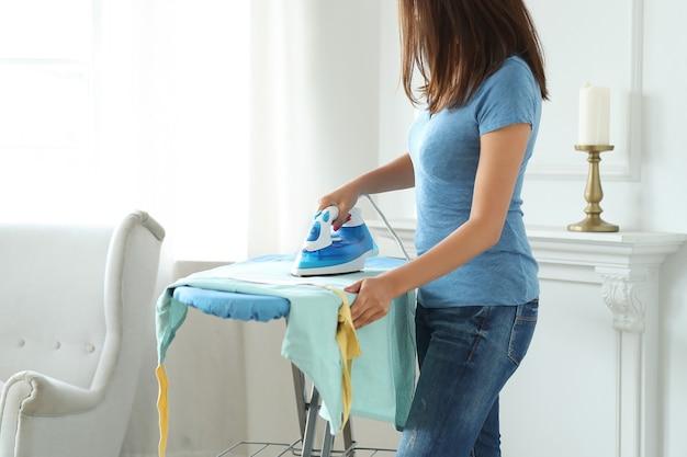 Młoda kobieta, prasowanie odzieży