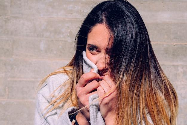 Młoda kobieta, prawdziwi ludzie, owijająca szyją płaszcz w słoneczny zimowy dzień.