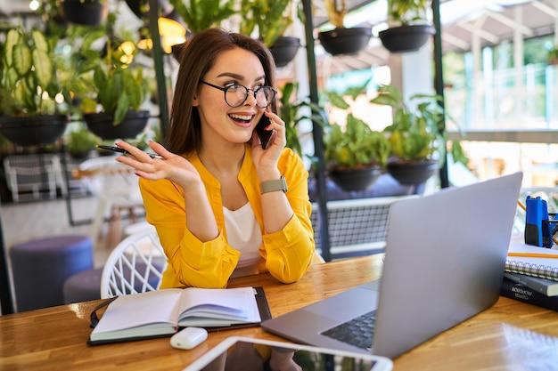 Młoda kobieta preety pracująca w domu i mówiący telefon komórkowy.