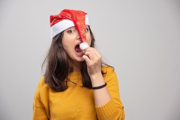 Młoda kobieta próbuje jeść czerwony kapelusz świętego mikołaja.