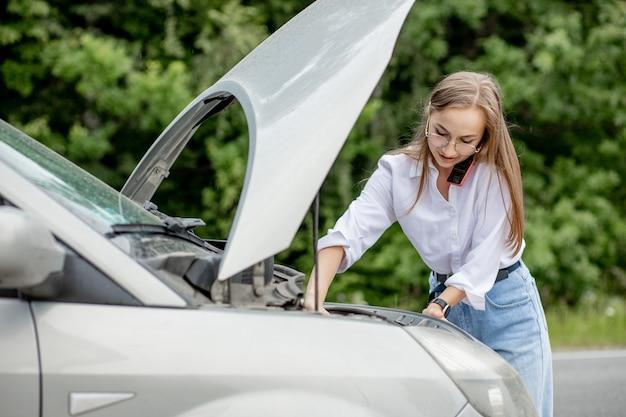 Młoda kobieta próbuje naprawić uszkodzony pojazd