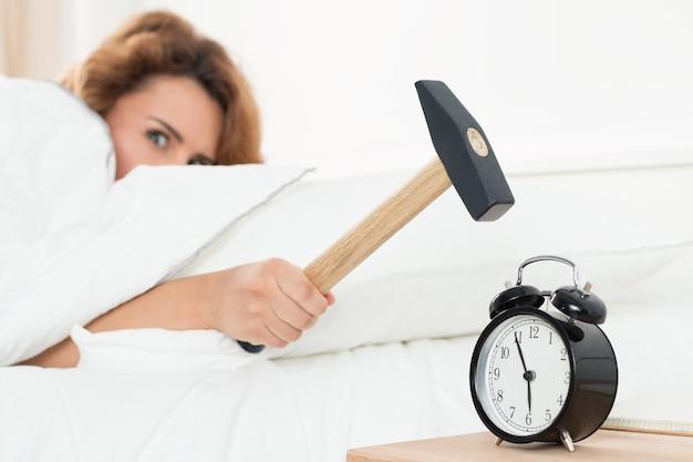 Młoda kobieta próbuje przełamać alarm młotkiem