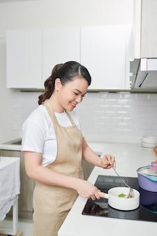 Młoda kobieta próbuje swoich potraw w kuchni