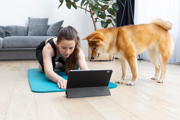 Młoda kobieta próbuje uprawiać sport w domu ze swoim psem