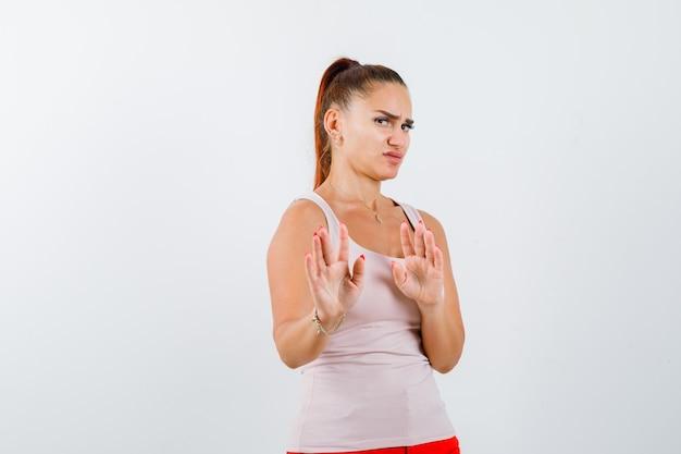 Młoda kobieta próbuje zasłonić się rękami w podkoszulku i źle wygląda, widok z przodu.