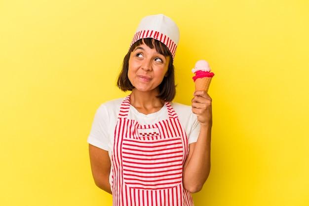 Młoda kobieta produkująca lody mieszanej rasy trzymająca lody na żółtym tle marząca o osiągnięciu celów i celów