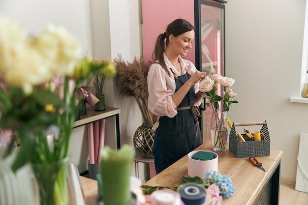 Młoda kobieta profesjonalnej kwiaciarni robi bukiety w kwiaciarni