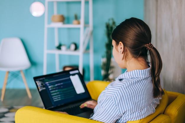 Młoda kobieta programista mobilny z laptopem, pisze kod programu na komputerze, programista pracuje w nowoczesnym biurze.
