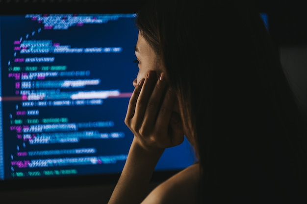 Młoda kobieta programista pisze kod programu na komputerze