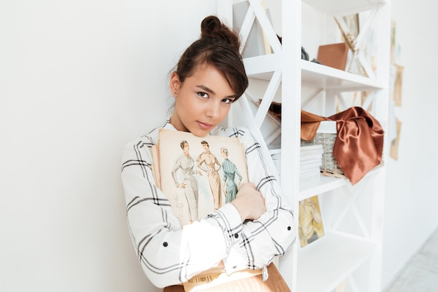 Młoda kobieta projektant mody gospodarstwa szkicownik