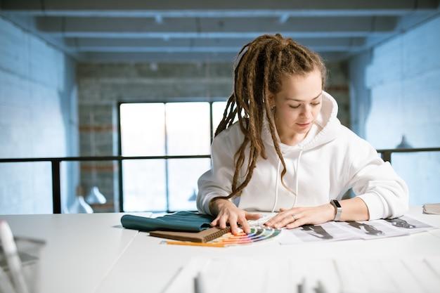Młoda kobieta projektant mody patrząc na szkice na biurku, wybierając kolory do nowej kolekcji w studio