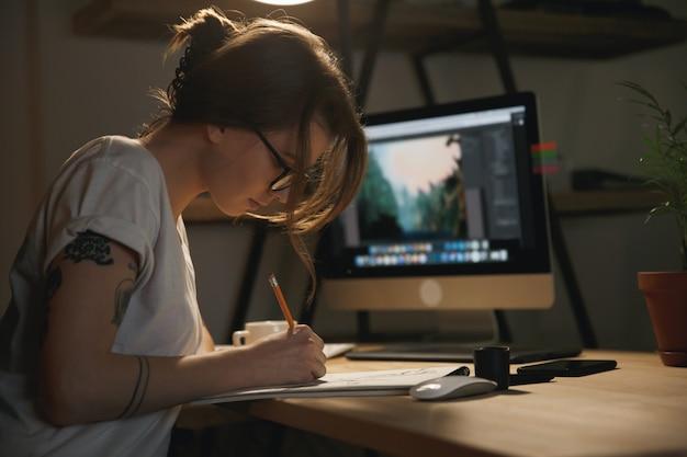 Młoda kobieta projektant siedzi w pomieszczeniu w nocy, rysując szkice