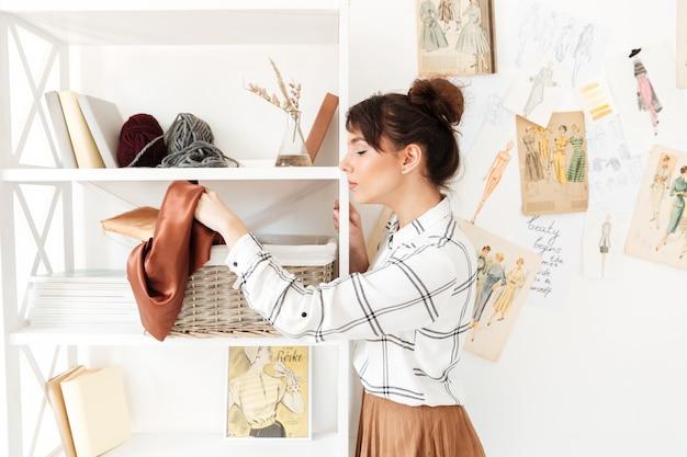 Młoda kobieta projektant wybiera materiał tekstylny dla jej pracy