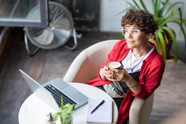 Młoda kobieta projektant z filiżanką kawy siedzi w fotelu w kawiarni przed laptopem, relaksując się i ciesząc się wypoczynkiem