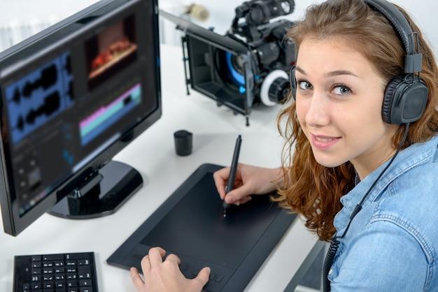 Młoda kobieta projektant za pomocą tabletu graficznego do edycji wideo