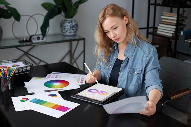Młoda kobieta projektantka logo pracująca na tablecie graficznym