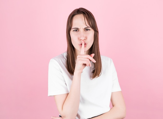 Młoda kobieta prosi o ciszę z palcem na ustach. cisza i sekretna koncepcja na różowym tle,