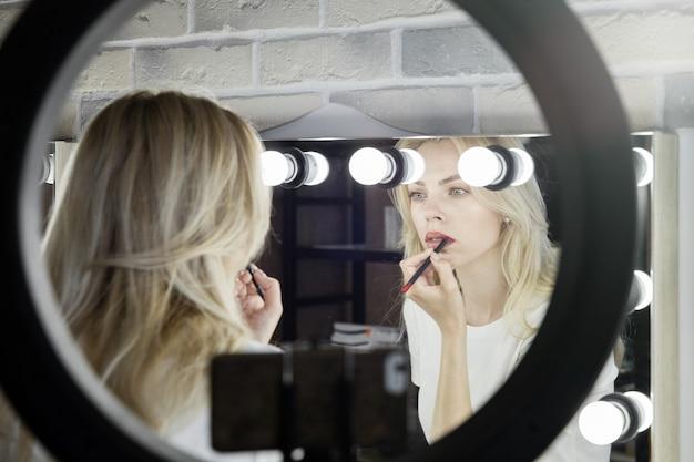 Młoda kobieta prowadzi online mistrzowskie lekcje makijażu w gabinecie kosmetycznym