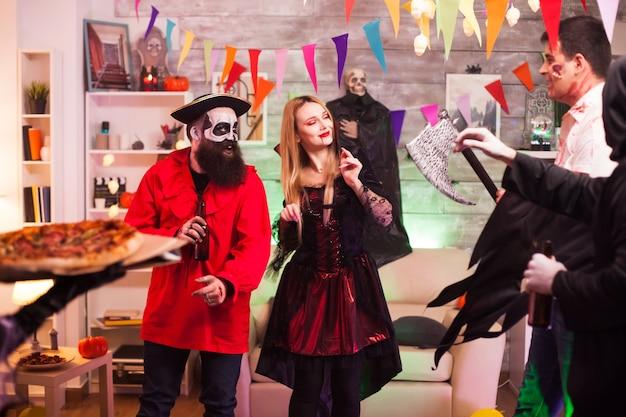 Młoda kobieta przebrana za wiedźmę na halloween przybywa z pizzą na imprezę.